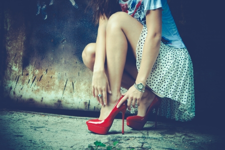 fashion shoes: woman legs in red high heel shoes and short skirt outdoor shot against old metal door