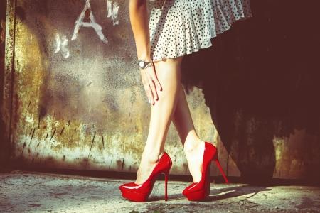 Frau Beine in roten Schuhen mit hohen Absätzen und kurzen Rock im freien Schuss gegen alte Metalltür