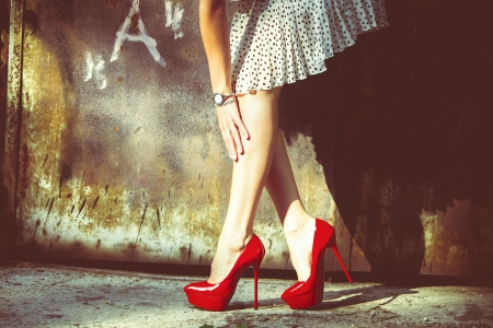 retro fashion: woman legs in red high heel shoes and short skirt outdoor shot against old metal door