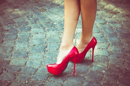 high street: woman legs in red high heel shoes outdoor shot on  cobble street Stock Photo