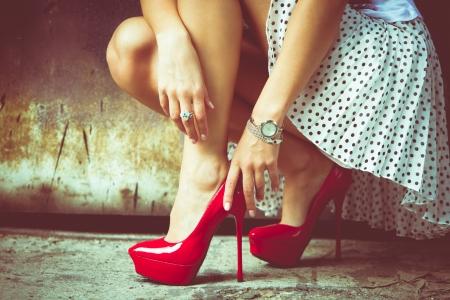 mode: vrouw benen in rode hoge hakken en korte rok buiten schot tegen oude metalen deur Stockfoto