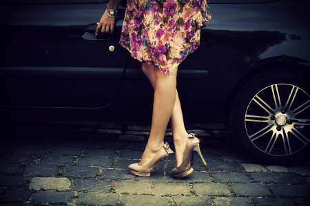 elegant woman in high heel shoes getting into car photo