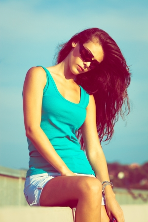 tank top: young woman in blue top tank and sunglasses outdoor shot sunny summer day