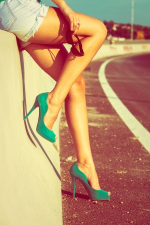 woman tan legs in high heel green shoes outdoor shot  summer day photo