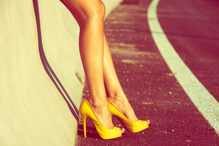 high day: woman tan legs in high heel yellow shoes outdoor shot  summer day Stock Photo