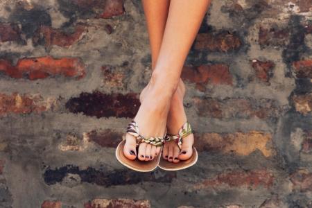 sandalias: piernas de la mujer en zapatillas planas día de verano al aire libre tiro en la ciudad Foto de archivo
