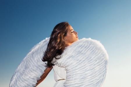 schöne junge Brünette Frau mit weißen Engelsflügeln gegen blauen Himmel bei Sonnenuntergang, Profil, Rücken geschossen, kleine Menge von Korn hinzugefügt Standard-Bild