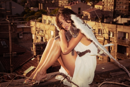 angelic: beautiful angel woman with white wings sit on roof edge holding cat, view of the city  in background