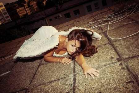 fallen: beautiful angel woman with white wings lie on roof
