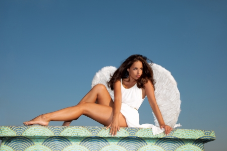 angelic: beautiful young brunette woman  with angel wings and white dress against blue sky,  full body shot outdoor