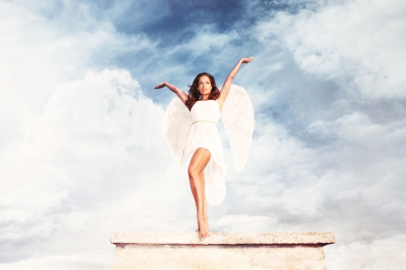 heavenly angels: beautiful goddess like young brunette woman  with angel wings and white dress against sky with clouds , full body shot, outdoor