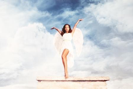 diosa griega: hermosa diosa como mujer joven morena con alas de ángel y vestido blanco contra el cielo con las nubes, el cuerpo el disparo, al aire libre