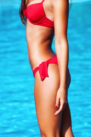 tanned woman body in red bikini blue water in background photo