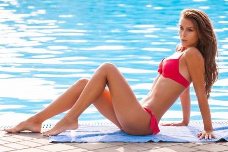 schöne junge Frau im Bikini am Pool entspannen Lizenzfreie Bilder