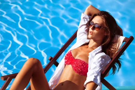sunbath: young beautiful  woman in bikini and sunglasses by the pool take sunbath