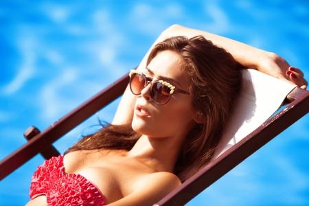 young beautiful young woman in bikini and sunglasses by the pool take sunbath photo