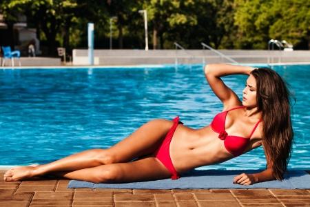 niñas en bikini: joven y bella mujer en bikini rojo en la piscina