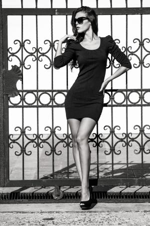 junge Frau in engen Kleid lean on schmiedeeisernen Zaun Ganzkörper bw