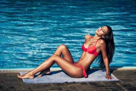 aantrekkelijke jonge vrouw in rode bikini bij het zwembad