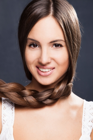 braided hair: smiling young natural looking woman with long healthy  braid hair