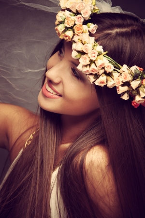 smiling young woman with wreath of flowers and veil in hair studio shot Stock Photo