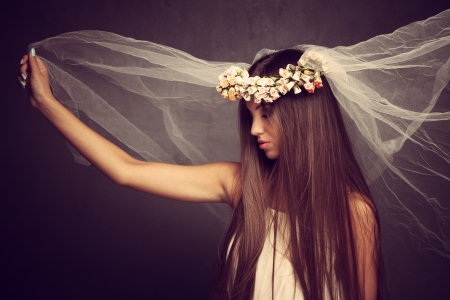 young beautiful woman with veil and wreath of flowers, profile, studio shot photo