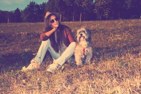 lächelnde junge Frau mit Hund sitzen auf der Wiese voller Retro-Farben