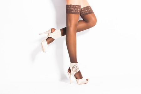 hold ups: woman legs in elegant brown lace hold ups stockings and high heel shoes studio shot