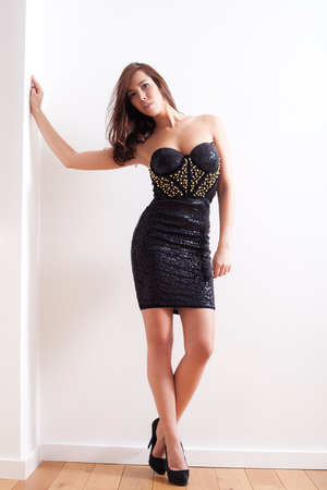 elegant young woman in mini cocktail dress with rivets  full body shot indoor Stock Photo - 22420403