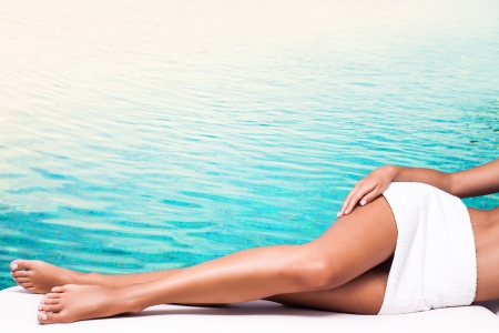 woman legs: perfect woman legs light blue water in background Stock Photo