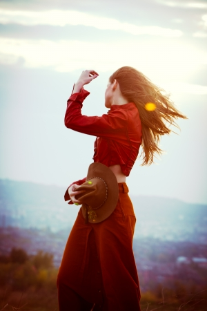 young woman in the wind stand on hill above the city wearing red leather jacket and long skirt hold hat in one hand  photo