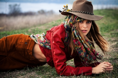 young blond woman in autumn fashion clothes, hat, red leather jacket, cashmere scarf and brown pants outdoor shot photo