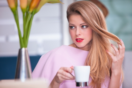 elegant young woman drinking coffee in cafe  photo