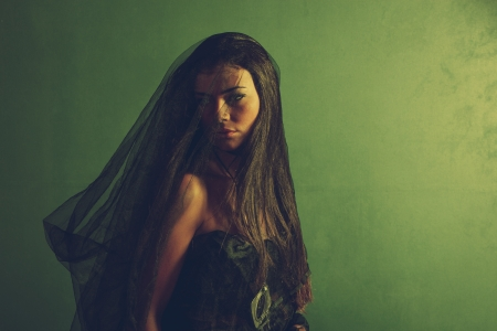 woman under black veil in front green wall  photo