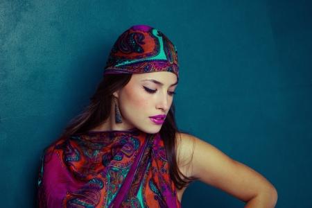 hermosa oriental mirada joven mujer con pañuelo sobre fondo azul