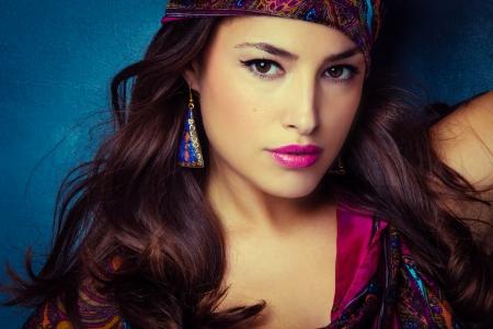 Beau regard oriental jeune femme avec un foulard sur fond bleu Banque d'images - 23452300