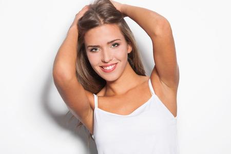 tank top: smiling modern natural beauty blonde straight hair girl in white top tank studio shot white background