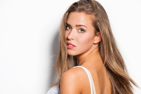 beauty shot: modern natural beauty blonde straight hair girl in white top tank studio shot white background Stock Photo