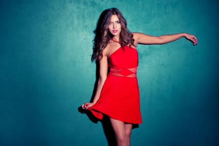 blue dress: girl in a red dress on blue wall studio shot Stock Photo