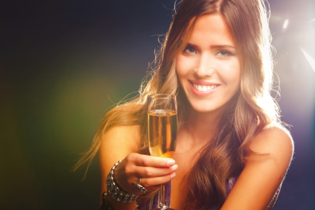 smiling young woman celebrating with champagne photo