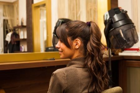 fodrászat: mosolygós fiatal nő frizurát a fodrászat