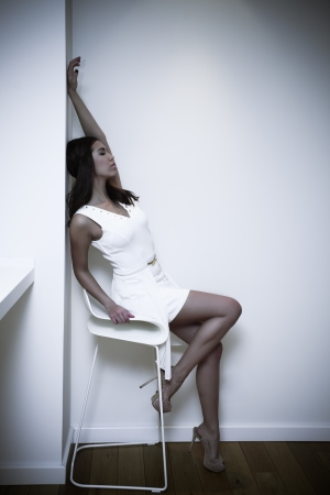 elegant woman in short white dress and high heel shoes indoor shot photo