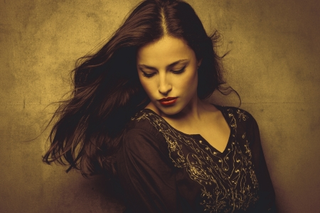 klassische Schönheit junge lange Haare brünett Frau in der bestickten T-Shirt in goldenen Tönen