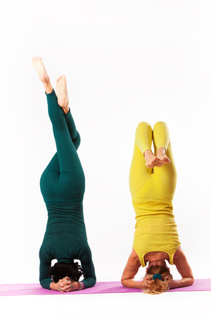 headstand: senior woman and younger woman practice yoga, headstand pose, studio shot