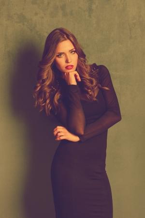 to tight: blonde elegant woman in black tight dress retro colors Stock Photo