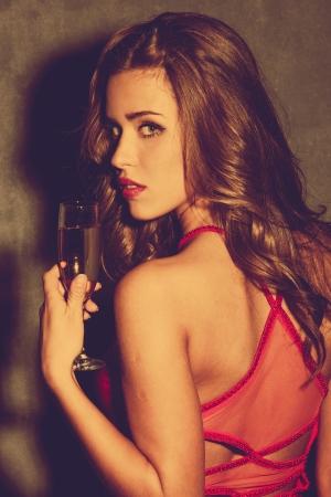 saúde: jovem mulher de vestido vermelho segurar um copo de cores champanhe retro