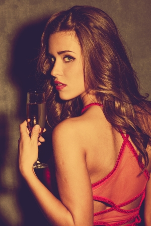 beautiful blonde girl with green eyes: young woman in red dress hold a glass of champagne  retro colors