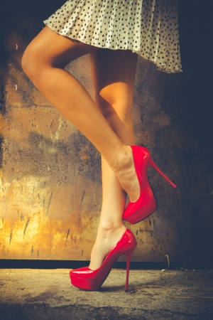 falda corta: piernas de la mujer en zapatos rojos de tac�n alto y falda corta de tiro al aire libre contra la vieja puerta met�lica Foto de archivo