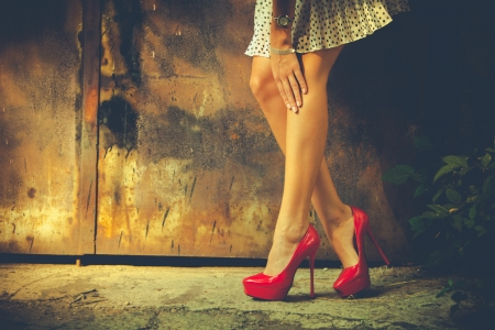 woman legs in red high heel shoes and short skirt outdoor shot against old metal door photo