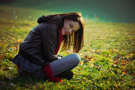 ordinary: young smiling ordinary  woman sit on grass on field